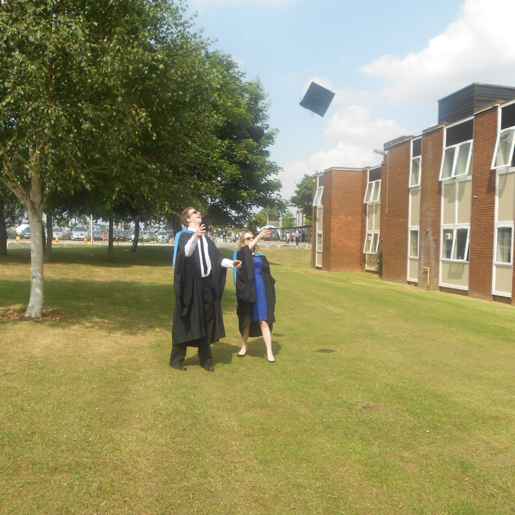 Photo of Liam and I on our graduation day, stood on the university campus, tossing our caps into the air.