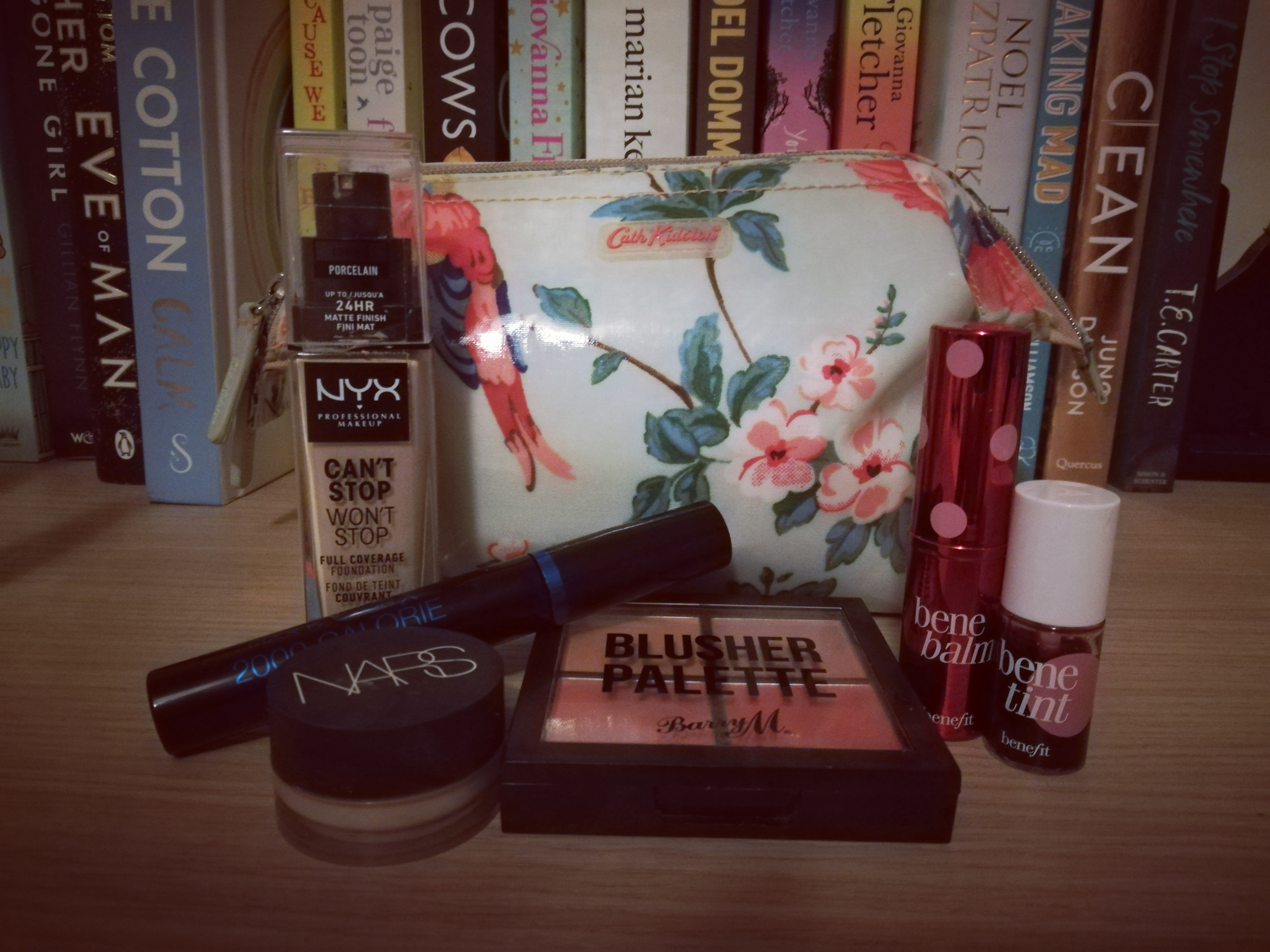 Picture of my makeup products in front of a Cath Kidston make-up bag. Left to right: NYX Can't Stop Won't Stop Foundation, MaxFactor 2000 Calorie Mascara, NARS Creamy Concealer, Barry M Blusher Quad Palette, Benefit Benebalm and Benetint.
