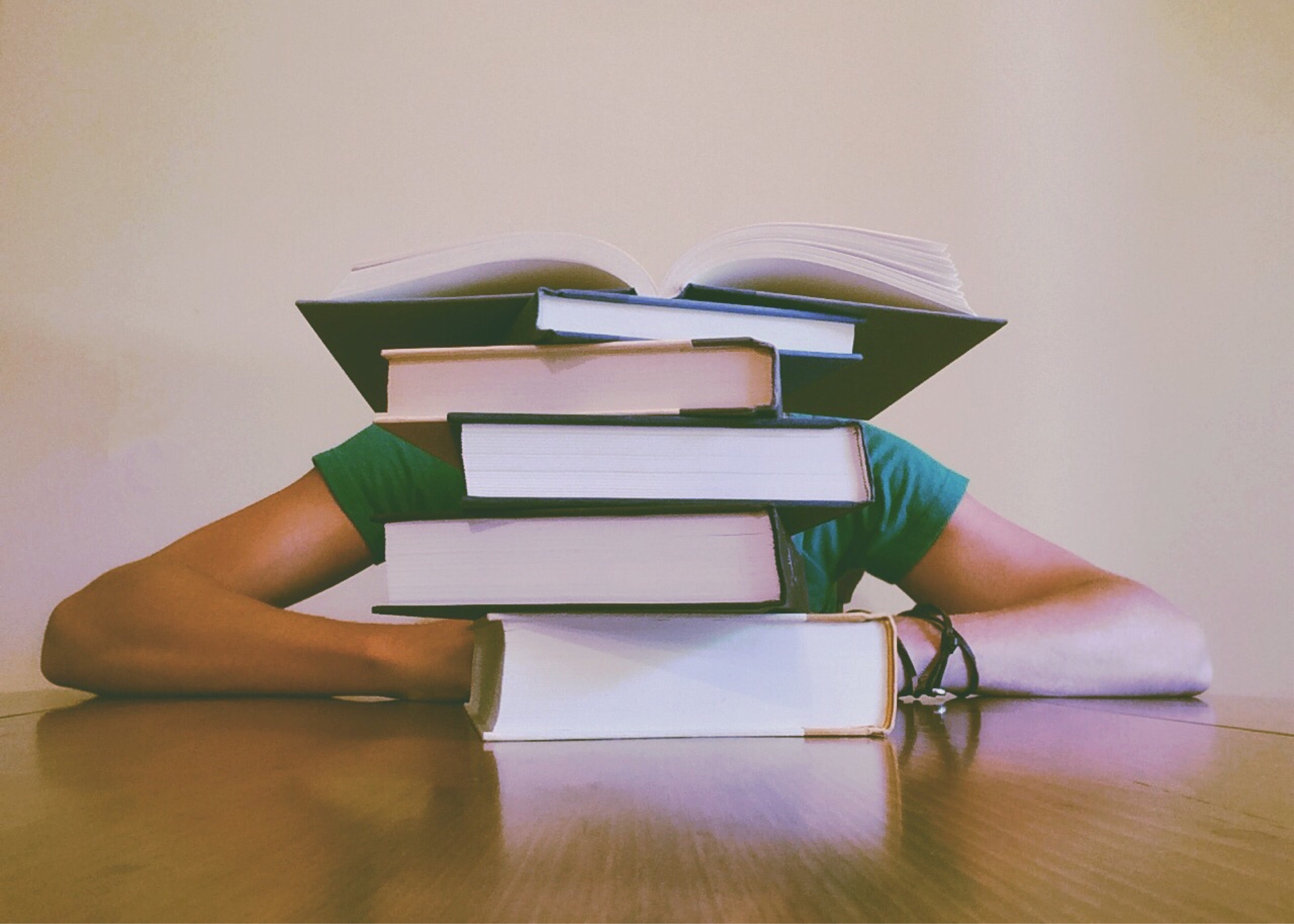Stock image of a person hiding behind a stack of textbooks.
