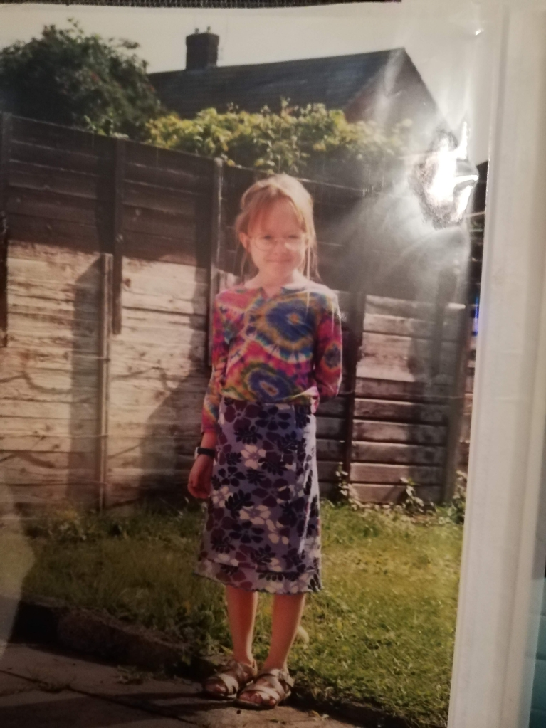 Photo of me aged 8, wearing a tie-dye top and purple floral skirt.