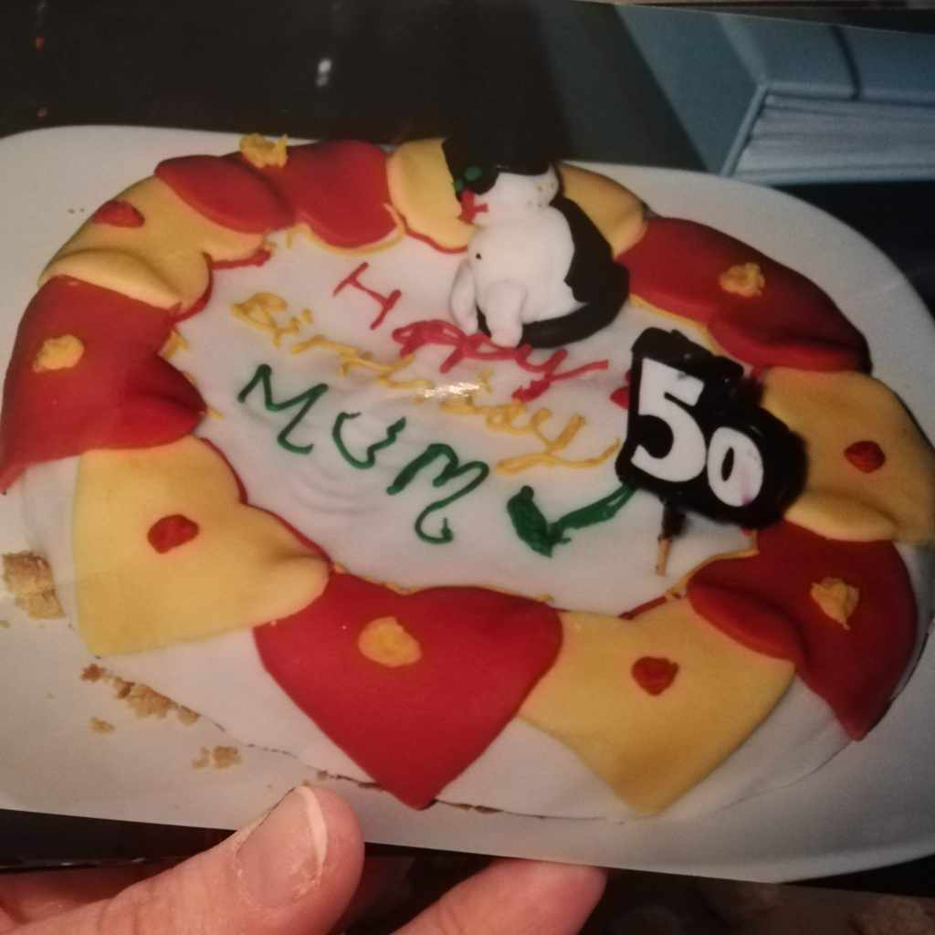 """A crappy attempt at a birthday cake I made for my Mum's 50th. It's supposed to be a while cake with red and yellow icing hearts and a royal icing cat on top. It says """"Happy Birthday Mum"""" in very shaky lettering, and generally looks like it's been thrown together."""