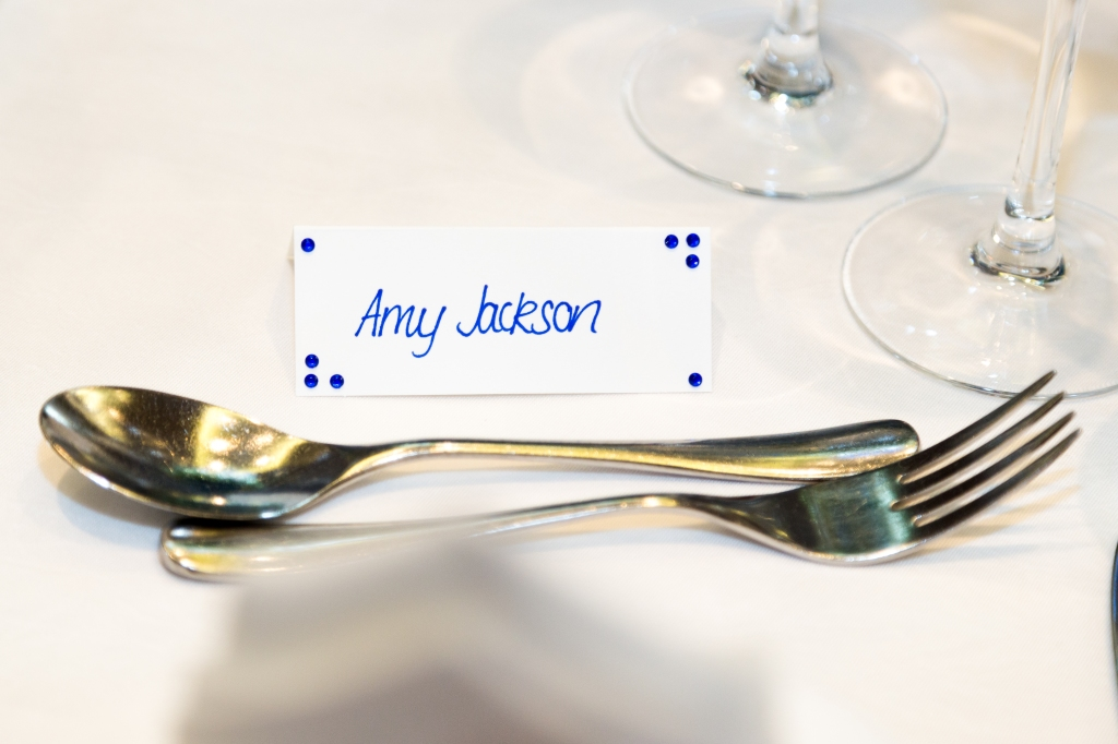 """A photo of my wedding place card on our dining table. It's a white piece of card with """"Amy Jackson"""" in blue italic handwriting along with tiny blue gemstones in each corner."""