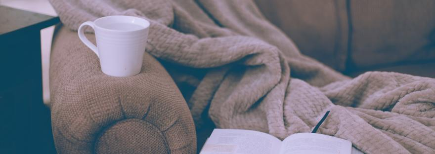 Picture of a sofa with a blanket, a mug, and an open book