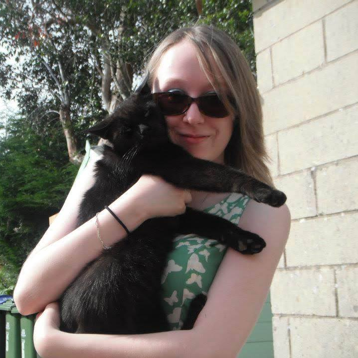 Photo of me smiling, wearing a green dress and sunglasses, holding Sooty in my arms.