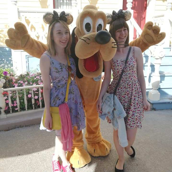 Photo of me and Lillie stood either side of Pluto on our trip to Disneyland.