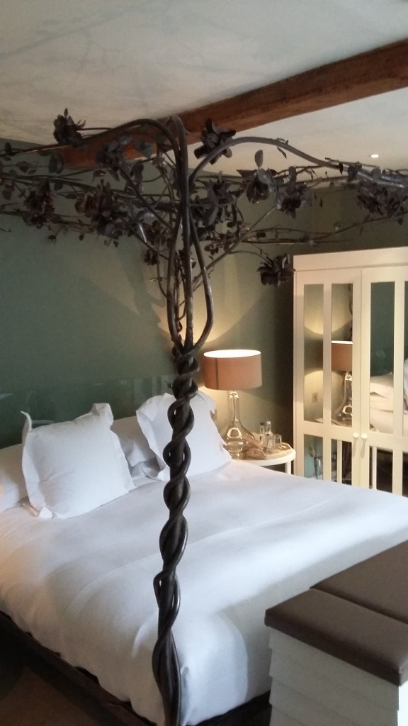 A photo of the bedroom at Barnsley House Hotel. The four-poster bed has a wire canopy decorated with metal leaves and the bed is covered in fresh white sheets with huge pillows.