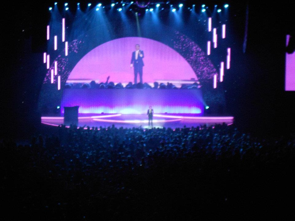 A photo I took from the back of the audience when I went to see Lee Evans' Roadrunner tour in 2011. You can see him from a distance on the stage, and he is also on the screen above the stage.