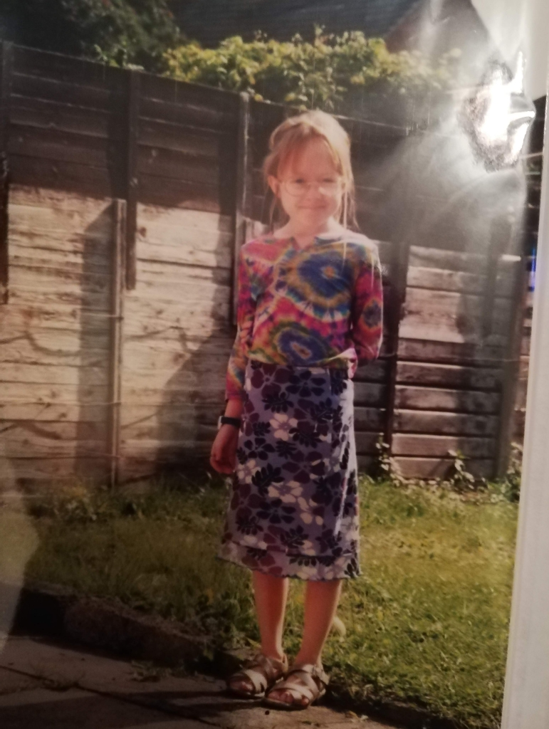 Me Age 8 wearing huge round glasses, a multi coloured tie-dye top and a purple floral patterned skirt. The look on my face says I am beyond thrilled with this outfit. It looks horrific.
