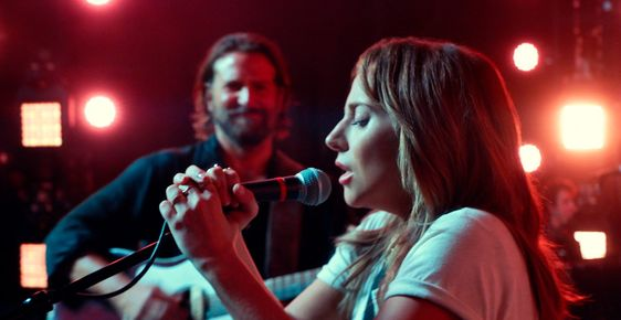 Screenshot from A Star is Born - Ally stands at the microphone and sings while Jack watches on, playing the guitar.