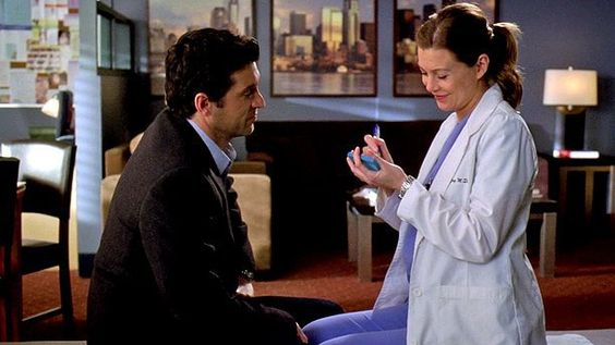 Screenshot from Grey's Anatomy - Meredith and Derek get married on a Post-It. Meredith smiles as she signs the Post-It while Derek watches.