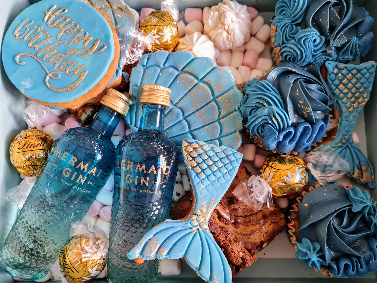 """Mermaid Box of Treats - There's three cupcakes decorated with blue icing, brownies, two mermaid tail shaped biscuits, a seashell shaped biscuit and a """"happy birthday"""" biscuit. Everything lies on a bed of mini marshmallows surrounded by meringues and gold Lindt balls, finished with two miniature bottles of Mermaid Gin."""