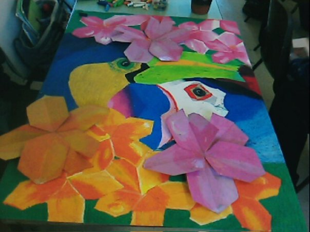 My exam piece for GCSE art - a picture of a toucan and a puffin in bright colours, surrounded by a combination of 3D flowers.