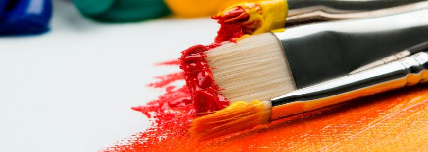 Close up of paintbrushes with paint on them, rest against a canvas.