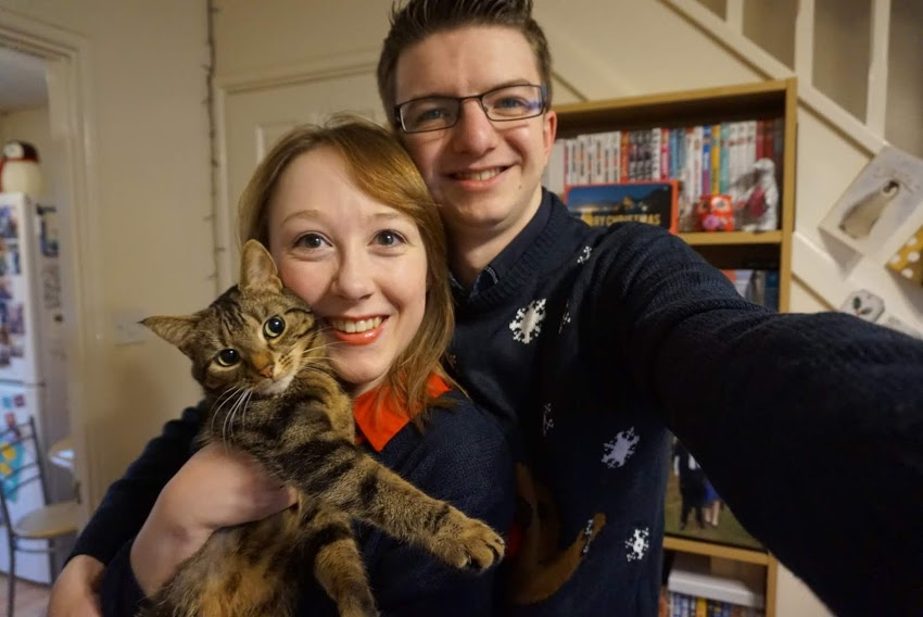 Christmas 2016 - Me, Liam, and Tilly. Liam and I are both smiling and dressed in Christmas jumpers, while Tilly is posing and looking at the camera.
